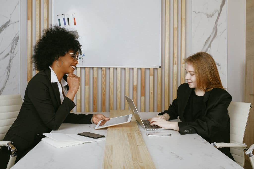 Two Woman sharing business ideas in business formal attire, while at meeting