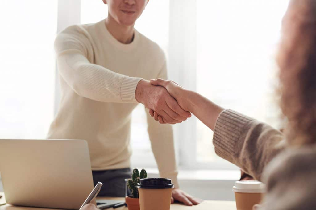 Client Shaking hand of business partner at meeting